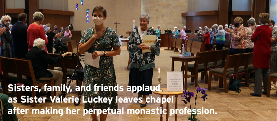 Sisters, family, and friends applaud as Sister Valerie Luckey leaves chapel after making her perpetual monastic profession.
