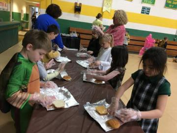 Kindergarteners and first graders from St. Luke's make sandwiches for the guests of Emmaus