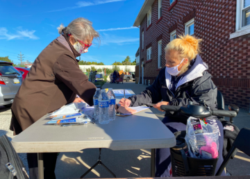 Cindy Purvis (left) helps a guest register to vote