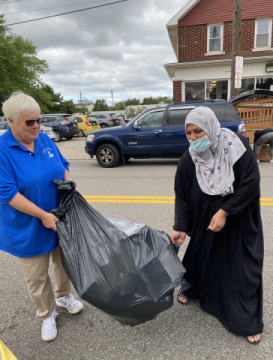 Sister Ann (L) and a guest carry items to the car