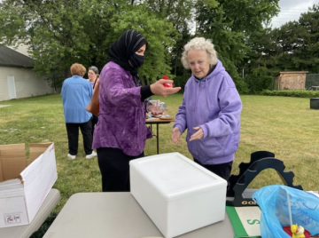 Sister Rosanne (R) helps a guest