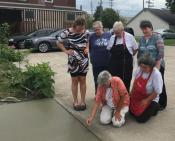 Members of Emmuas staff watch as Sister Mary Miller places the medal in the new circular driveway.