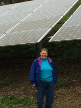 Sister Charles Marie, Physical Resource Director for the Benedictine Sisters and member of CARE, demonstrates the expanse of the ground-mounted solar installation in Corry.