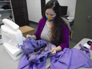 Cynthia Aulenbacher works on a dress for a wedding party.