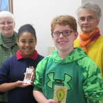 Art House students Teajanae and Garrett join CARE members Sisters Annette Marshall and Pat Lupo to show off student-made switch plate covers promoting energy conservation.