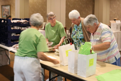 Sisters Chris and Karen Kosin, Claire and Lucia Surmik <br />prepare gift bags for golfers
