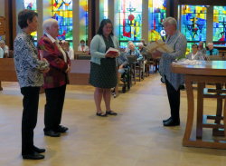 Sister Ann and Sister Stephanie present the two new novices with copies of the Rule of Benedict.