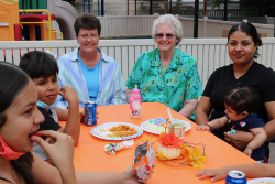 Sister Katherine, incoming director, and Sister Diane visit with a day care family.