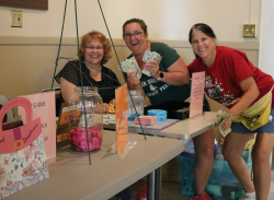 Darlene, Valerie, and Sue count earnings from<br />registrations and game ticket sales