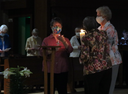 The single flame from the new fire is spread throughout the dark chapel.